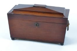 A Regency sarcophagus shaped tea caddy, raised on bun feet, the lid opening to reveal two