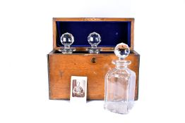 An oak Military Presentation tantalus, with three glass decanters and stoppers, having a plaque to