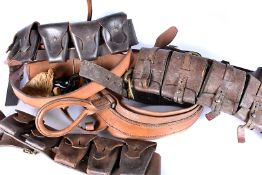 A collection of leather belts and ammo pouches, some having stamps, one very large example, having