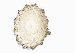 An early Victorian silver salver by DH CH, shaped rim with shells, engraved to well, on three