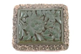 A Chinese and cinnabar lacquer clip, the green floral carved panel within a white metal mount marked