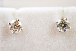 A pair of diamond ear studs, with post backs, brilliant cuts in four claw settings, total diamond