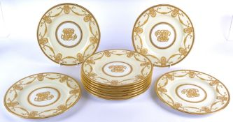 Eleven Copelands Spode china armorial plates, on a cream ground, with central hand painted roundel