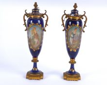 A pair of French porcelain covered jars with cartouches of beauties on a gilt blue ground, each with