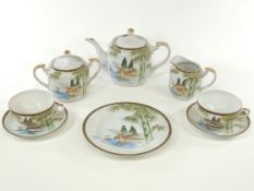 A Japanese porcelain tea set for six by the Kutani china factory, with typical landscapes and the