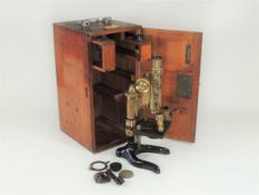 An Ernst Leitz Wetzlar early 20th Century mahogany cased brass and black lacquered microscope, model