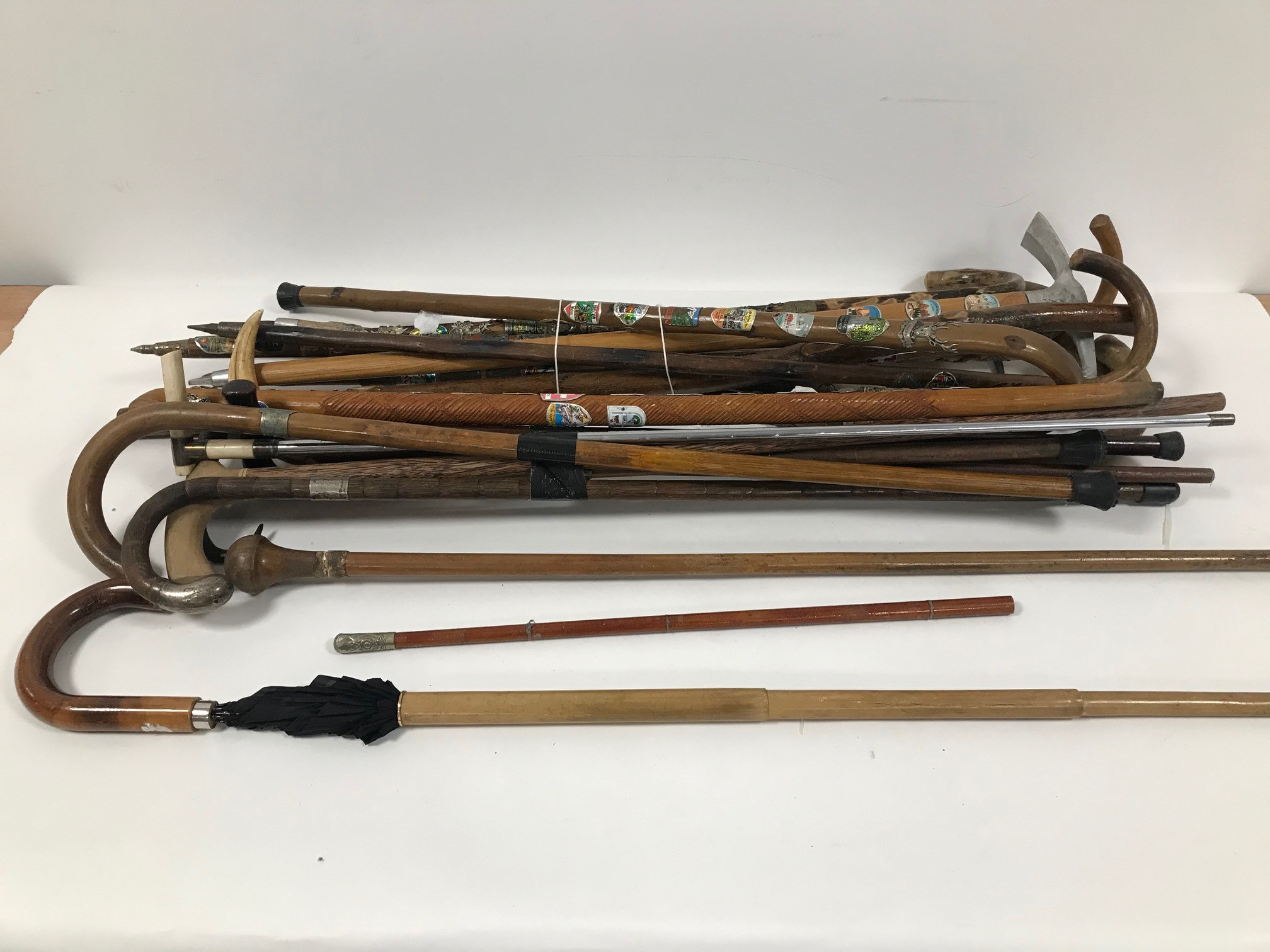 A collection of walking stick and canes, including a walking stick with removeable shaft to reveal
