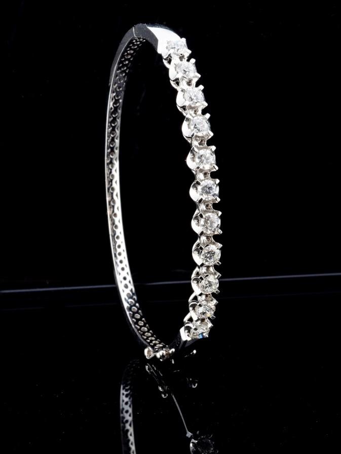 A modern pretty 18ct white gold and diamond bangle, having eleven brilliant cut diamonds in circular - Image 2 of 2