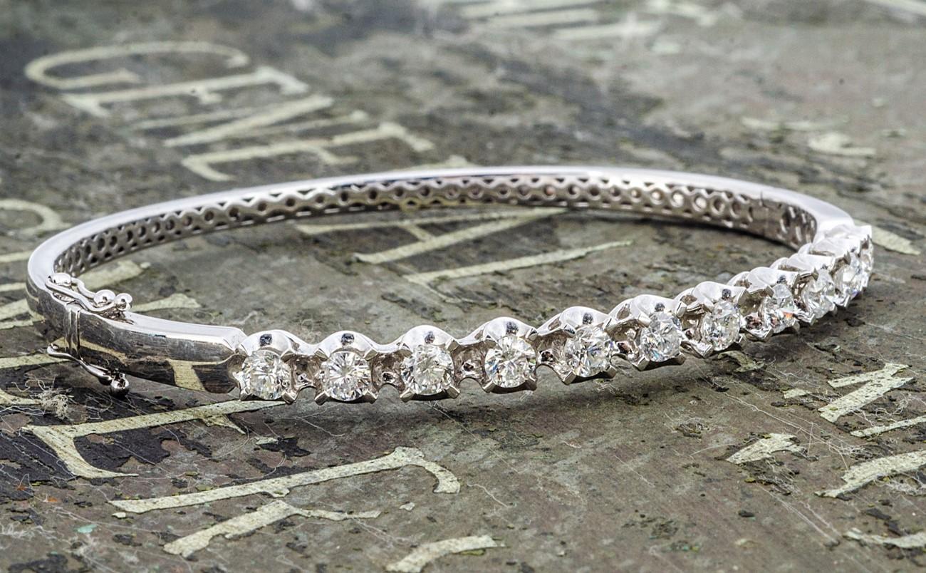A modern pretty 18ct white gold and diamond bangle, having eleven brilliant cut diamonds in circular
