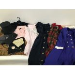 A collection of vintage clothes and other items, presented in a large wooden trunk and a London