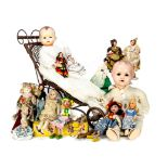 A collection of vintage dolls, together with a reproduction wicker dolls' push chair, 64cm high,