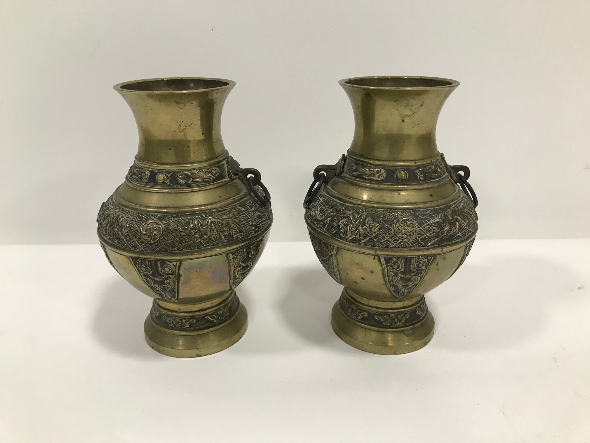 A pair of early 20th century Chinese brass vases, 19.5cm high, bulbous bodies with raised