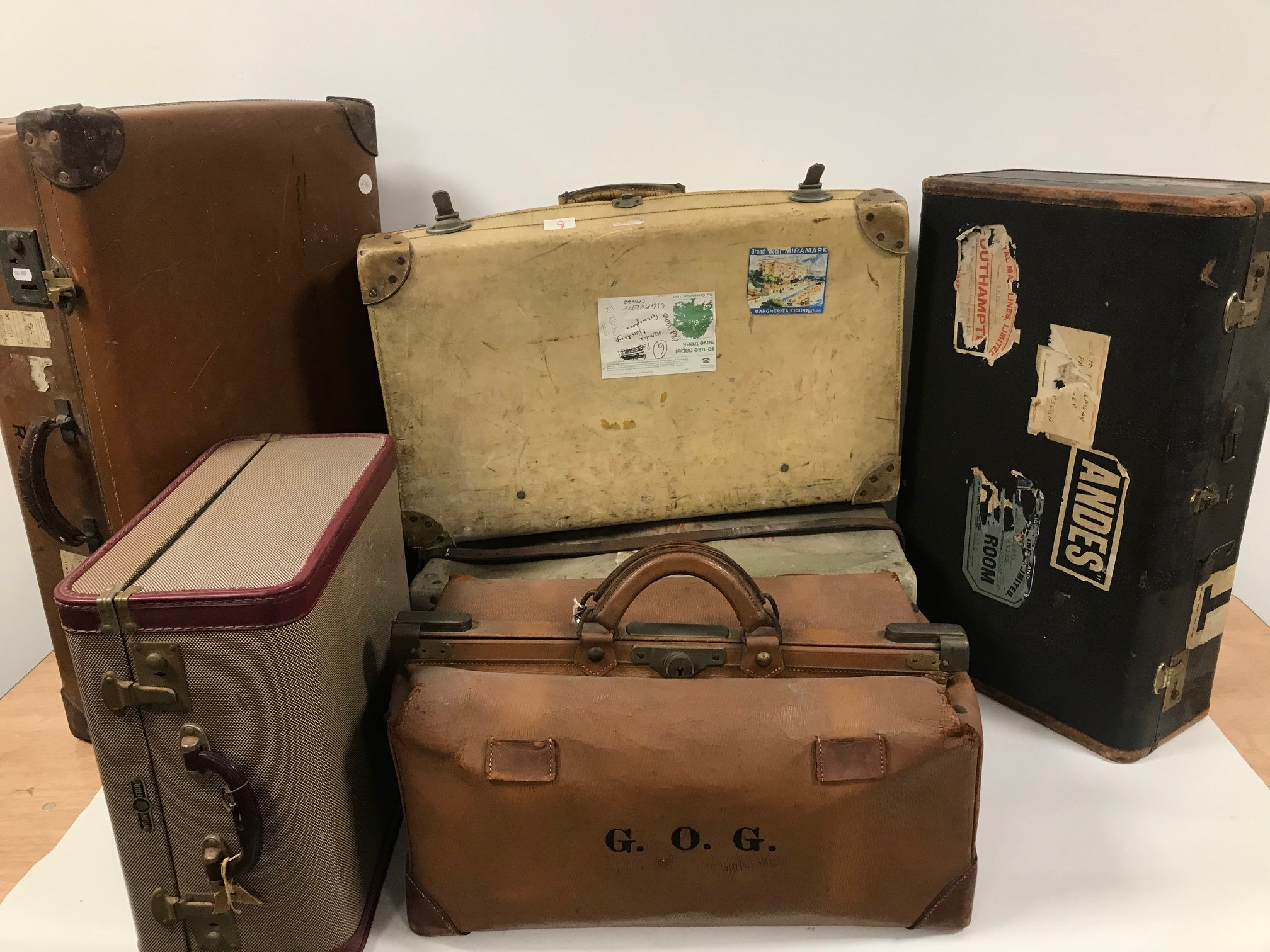 Five items of vintage luggage, including a doctor's style holdall, a white calf hide suitcase, a