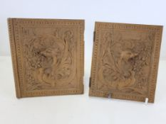 A pair of late 19th or early 20th Century Black Forest carved wooden book covers with a design of