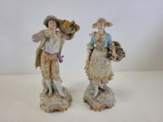 A pair of Continental porcelain figures with plentiful baskets of produce, one male, one female,