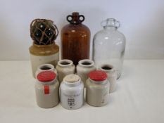 Two glass demi-johns one clear one brown, height 33cm, together with a dumpy green glass float and