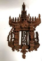 A South East Asian wall carving of architectural form with multiple miniature crouching and winged