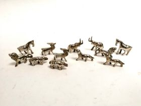 A group of Indian white metal menu holders, taking the form of wild animals including elephant,