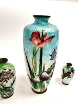 A group of three Japanese enamelled metalwork vases, each with a naturalistic floral design on a