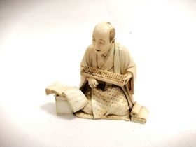 A Japanese Meiji period ivory okimono of a seated figure with an abacus and open book, with