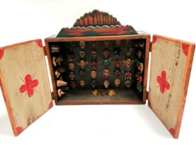 A South East Asian polychrome wall cabinet opening to reveal a series of mythical mask heads, 43cm x