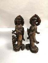 A pair of South East Asian gilt and polychrome figures of female immortals raised upon dragons,