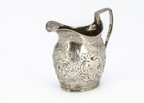 A George III silver milk jug, helmet shaped with later embossed design and repair to handle, marks