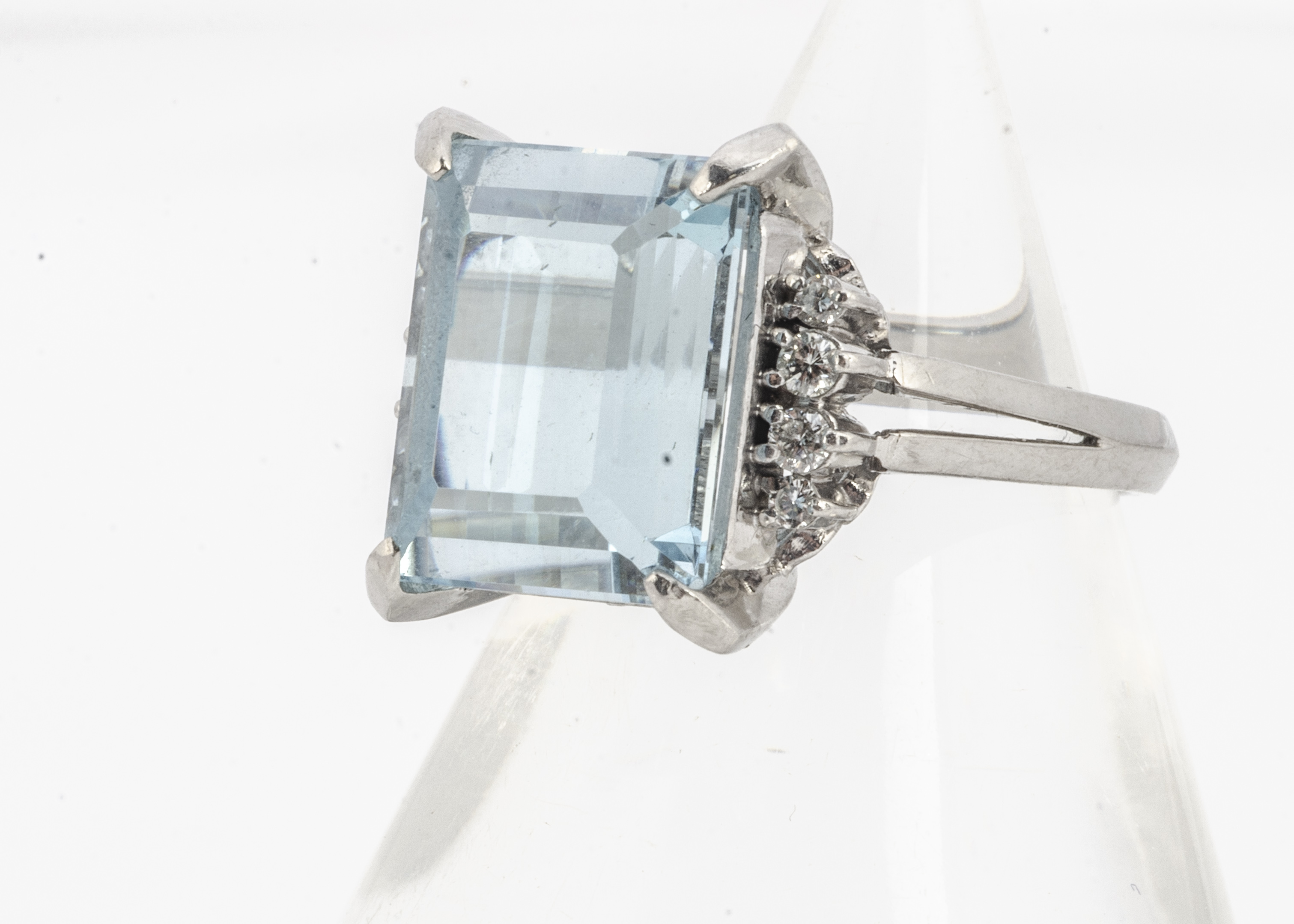 An aquamarine and diamond dress ring, the mixed step cut aquamarine flanked by brilliant cut