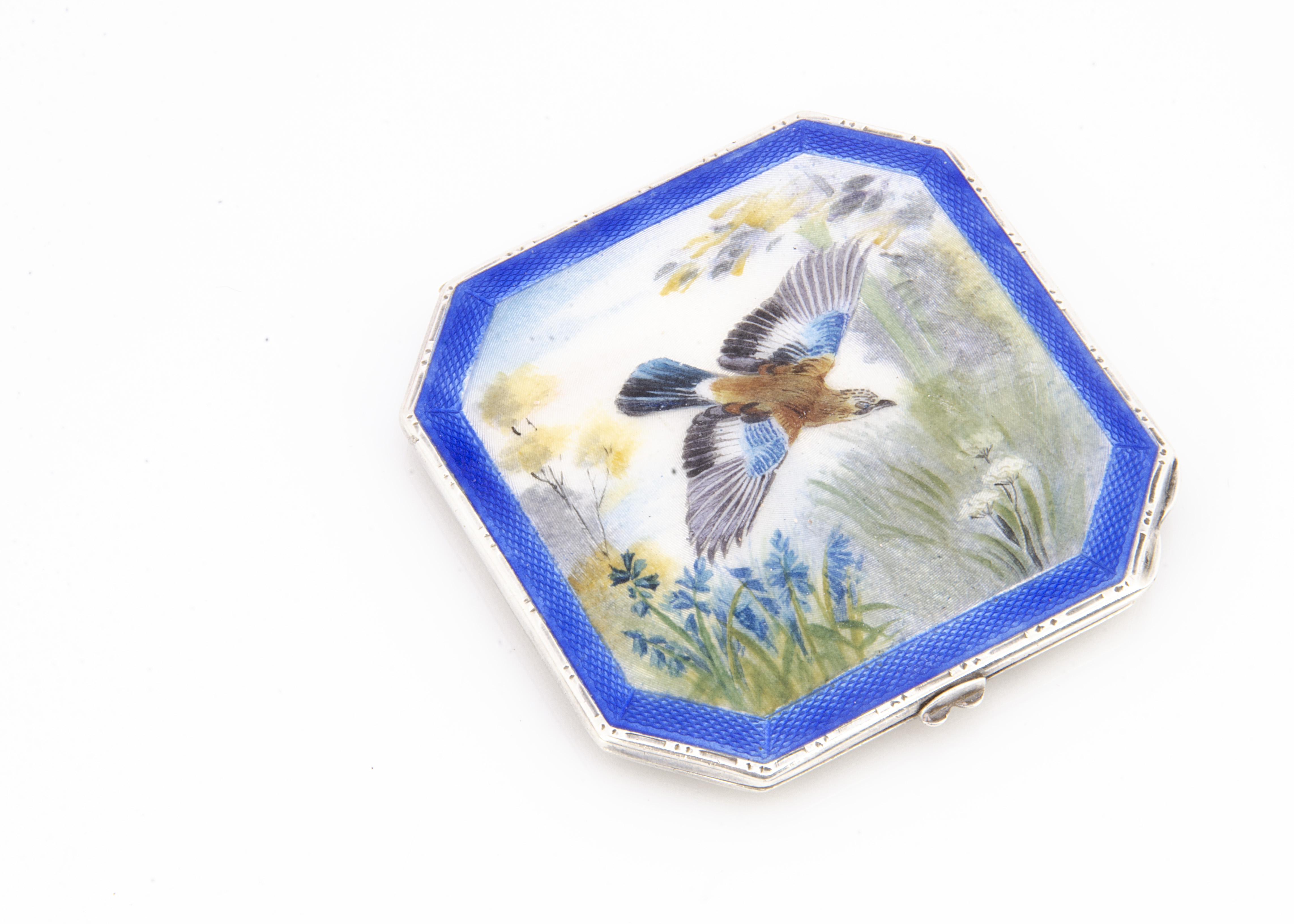An Art Deco period silver and enamelled compact by NCD, having swooping jay amongst flowers to