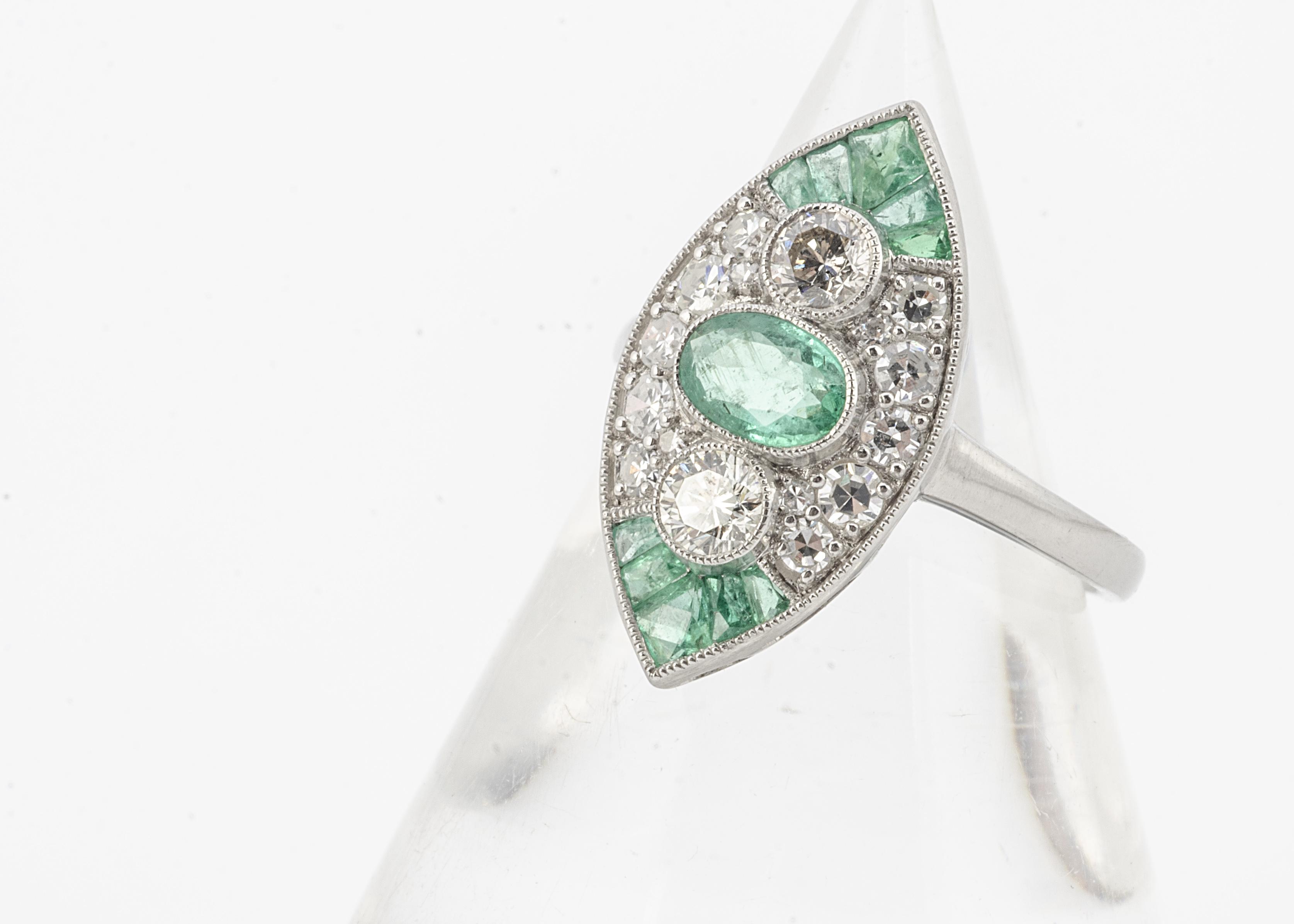 An Edwardian style platinum set emerald and diamond navette shaped ring, emeralds 0.75ct, diamonds