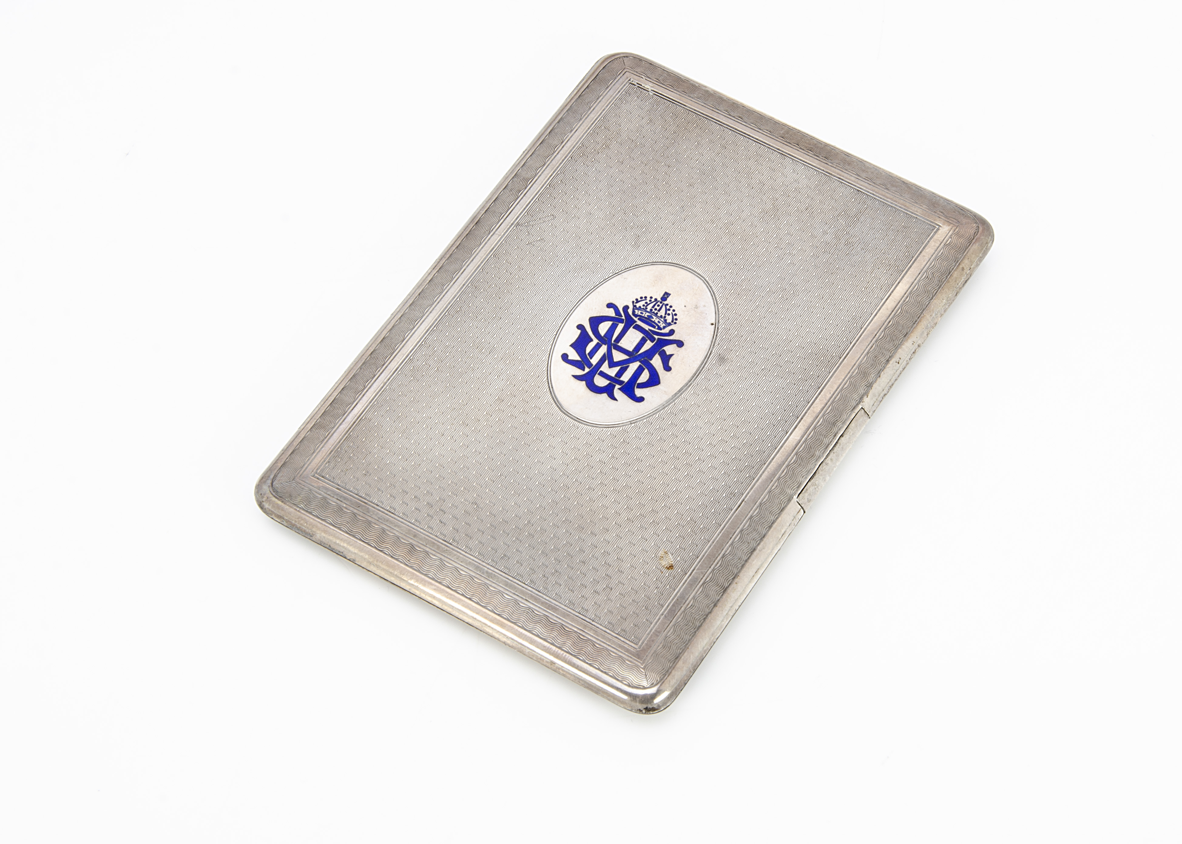 An Art Deco silver cigarette case by WFW, engine turned having blue enamel monogram and coronet, 5.7