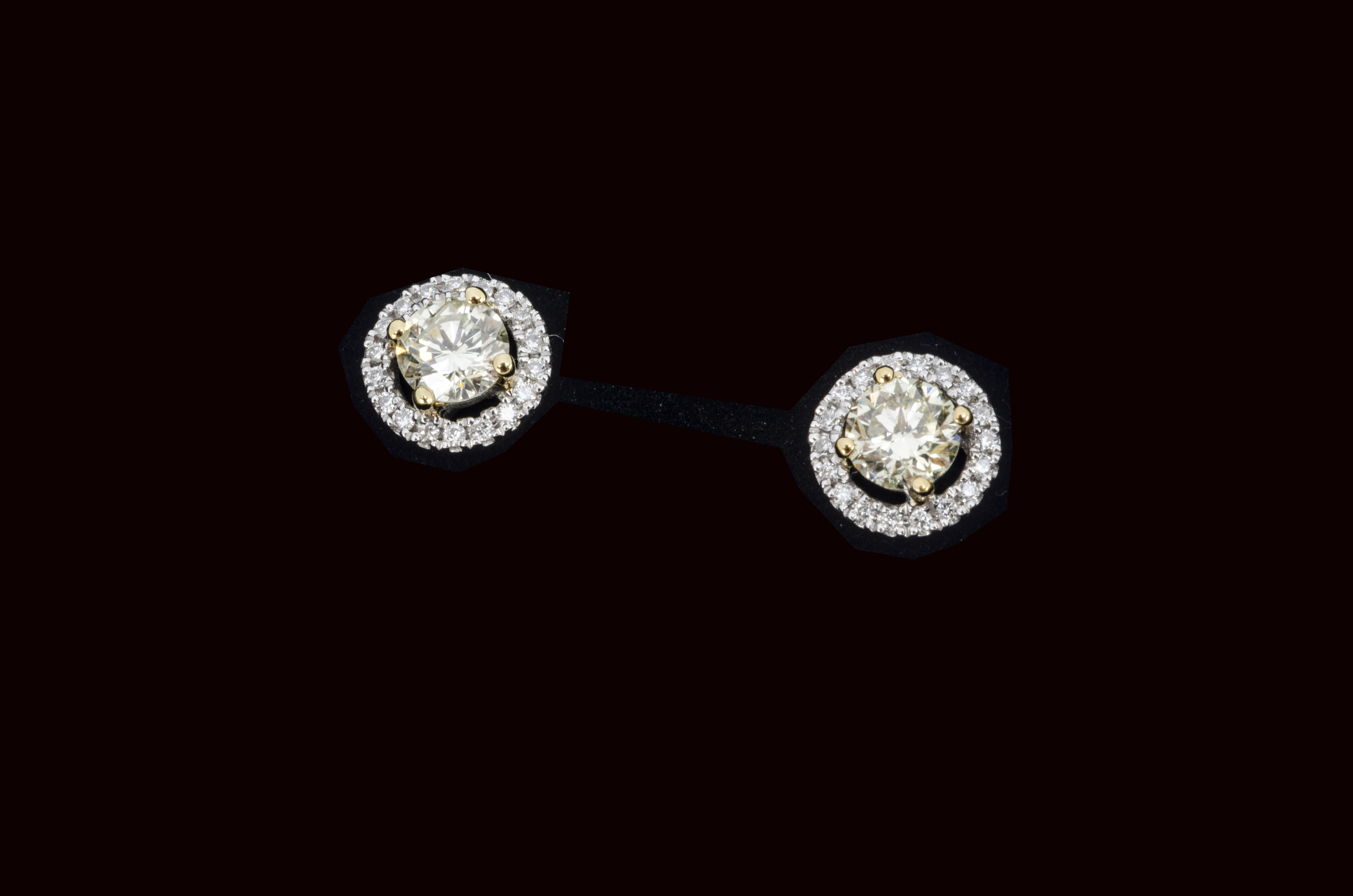 A pair of certificated yellow diamond brilliant cut colourless diamond ear studs, the round