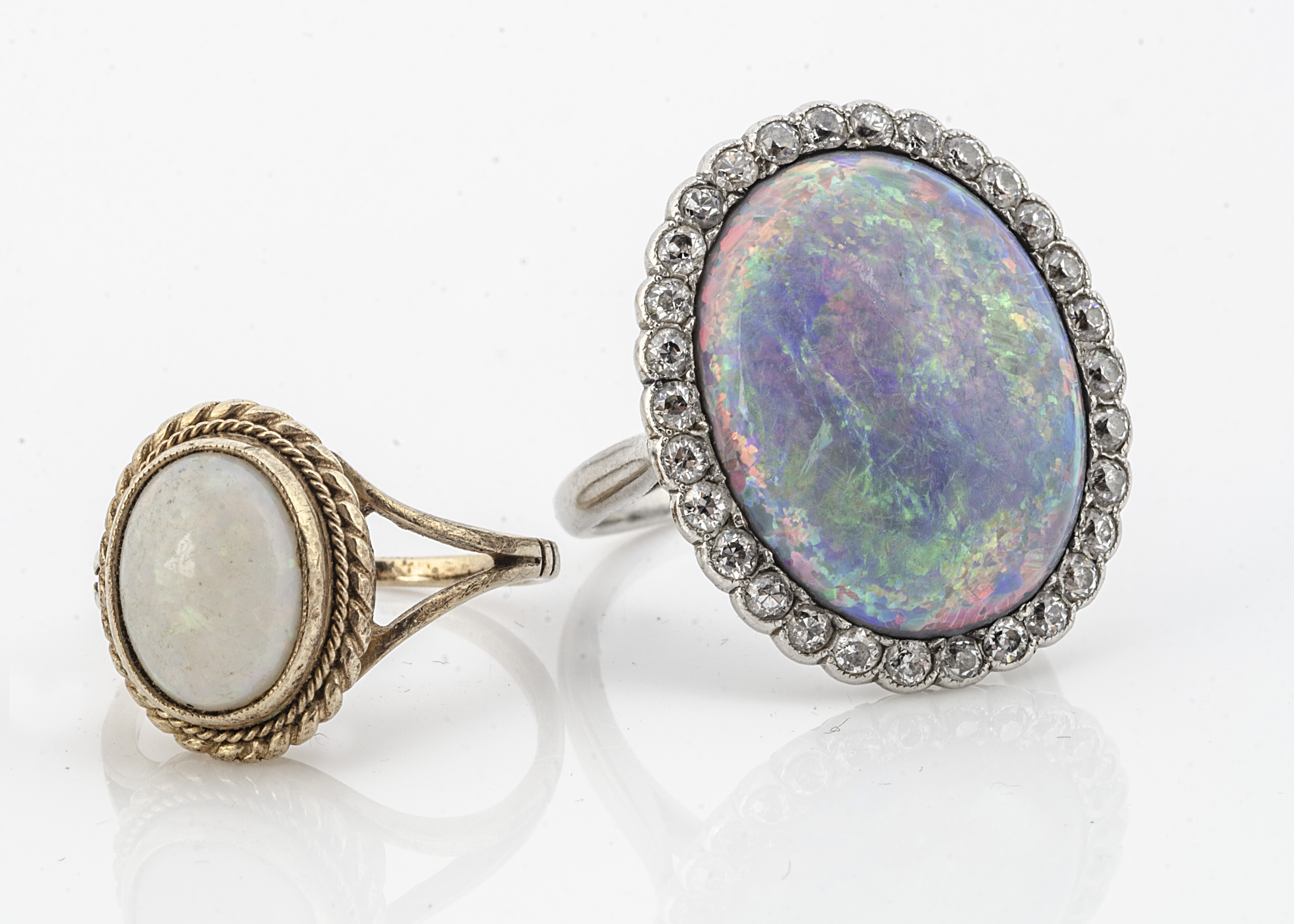 A large black opal and diamond bezel set dress ring, in white metal, the oval black opal with old