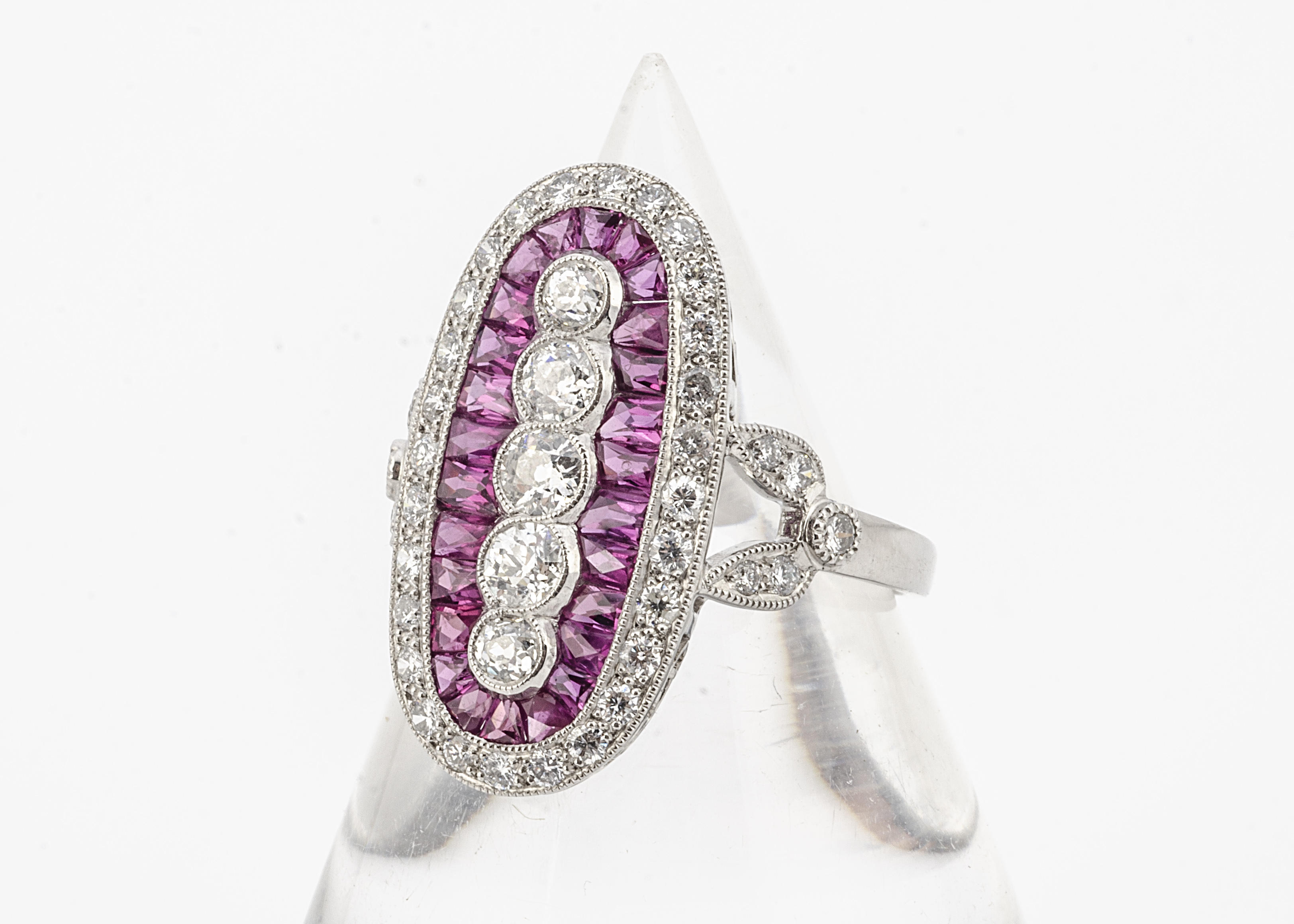 An Art Deco style ruby and diamond platinum set dress ring, of oval design with central band of