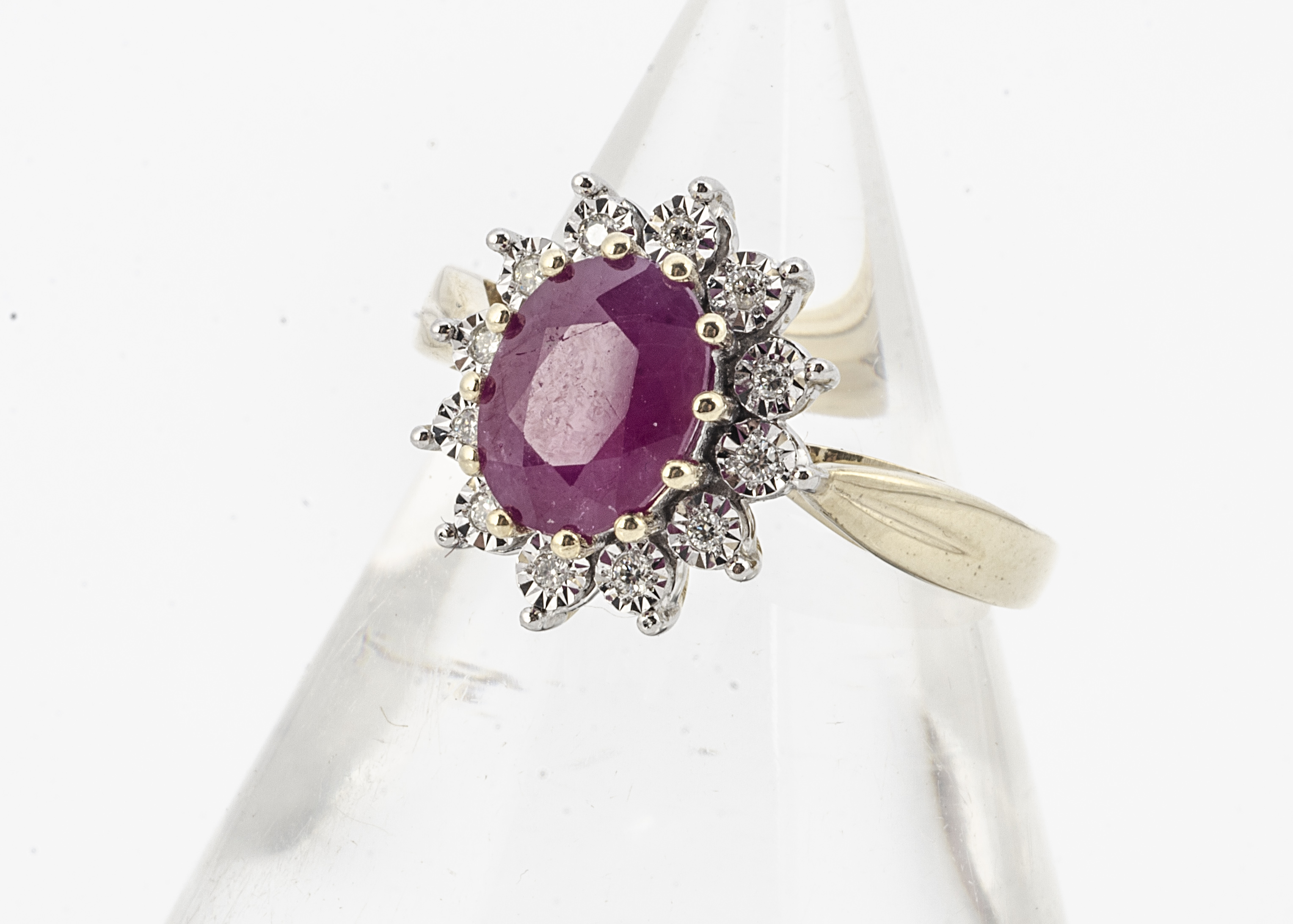 A 9ct gold ruby and diamond cluster ring, the opaque ruby surrounded by illusion set brilliant cut