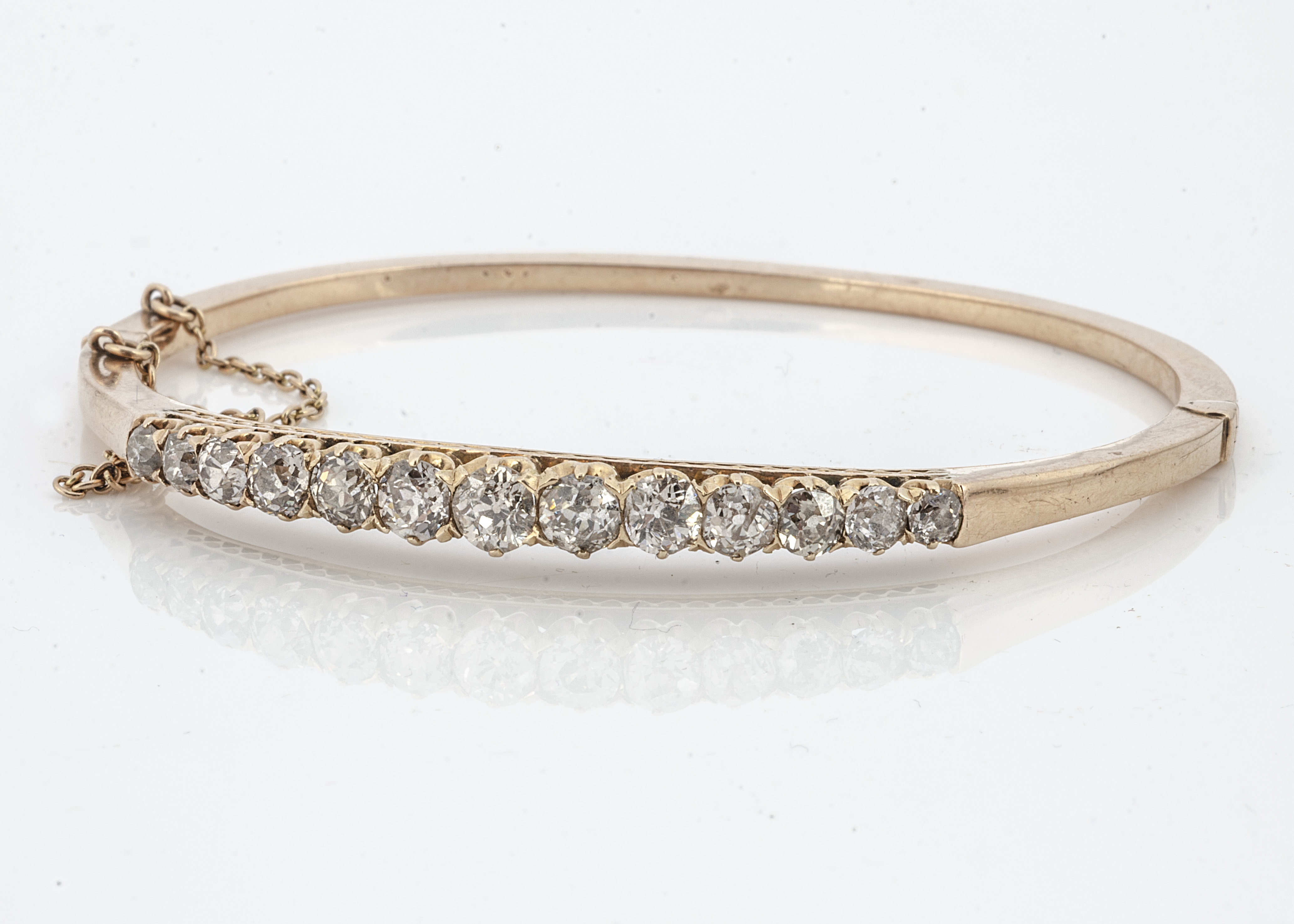 A French early 20th Century diamond set hinged bangle, the old cut claw set diamonds all in yellow
