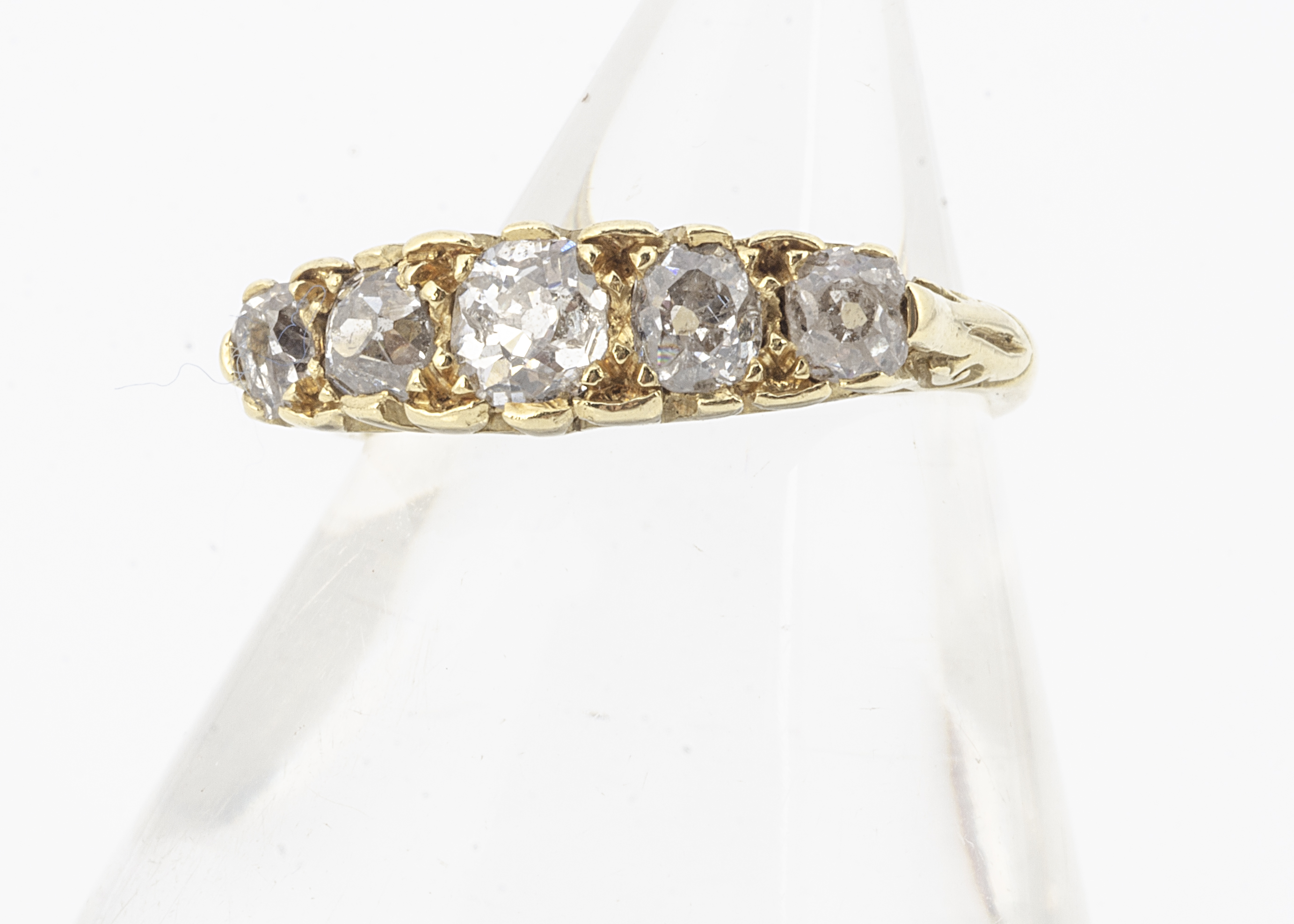 An 18ct gold five stone diamond ring, the old cut diamonds in claw settings with scroll gallery,