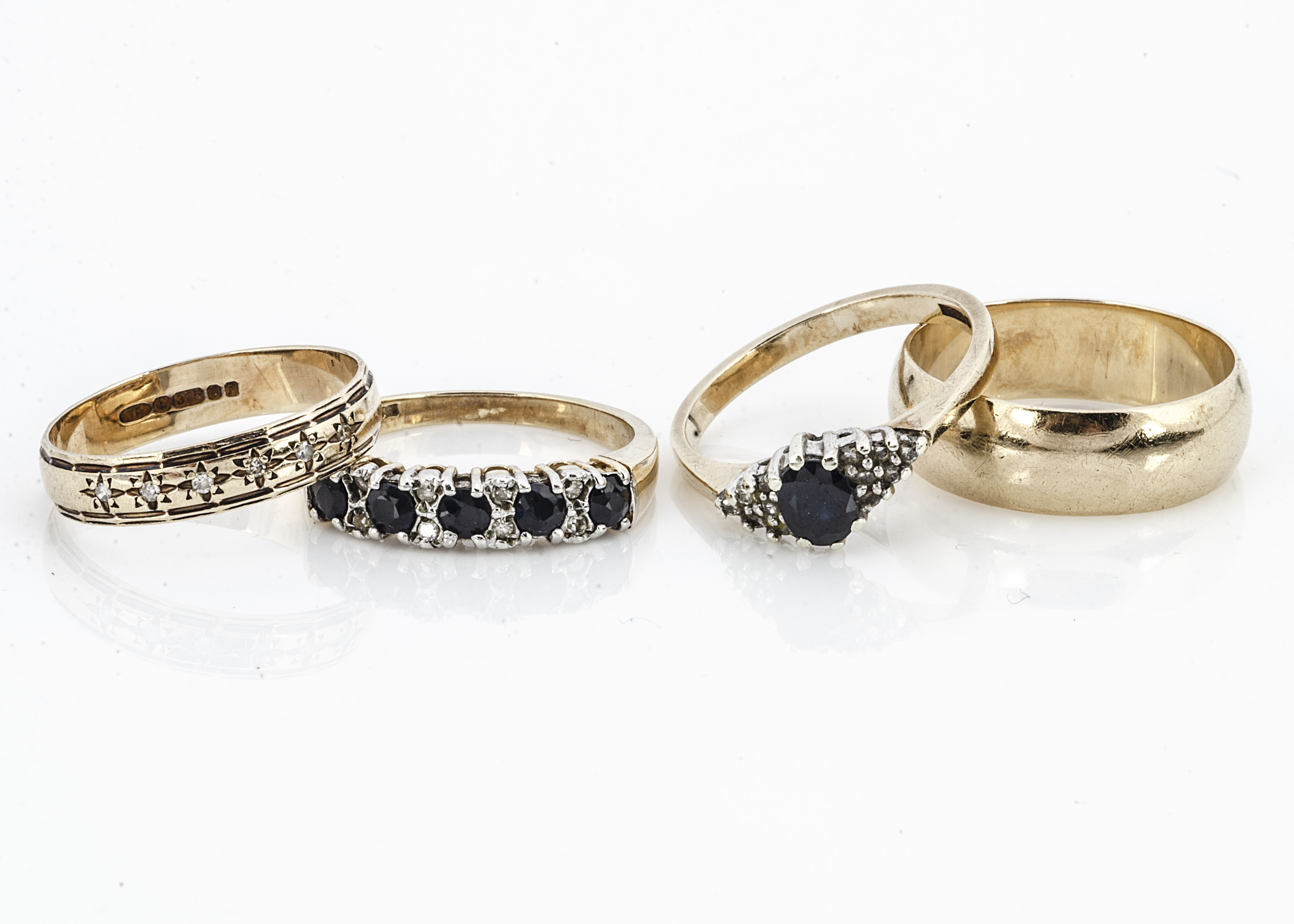 Four 9ct gold rings, two wedding bands one of curved plain form, ring size O, the other set with