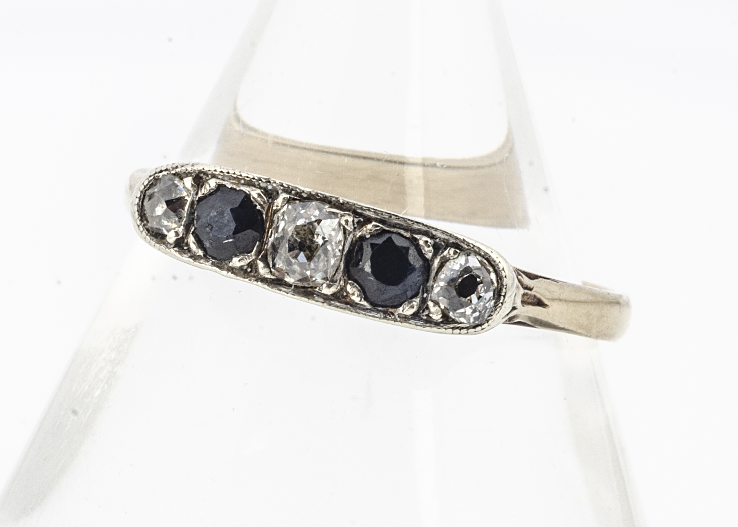 A 9ct gold sapphire and diamond five stone dress ring, old cut diamonds alternately set with blue