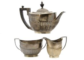 An Edwardian silver three piece tea set from Goldsmiths & Silversmiths, helmet shaped with fluted
