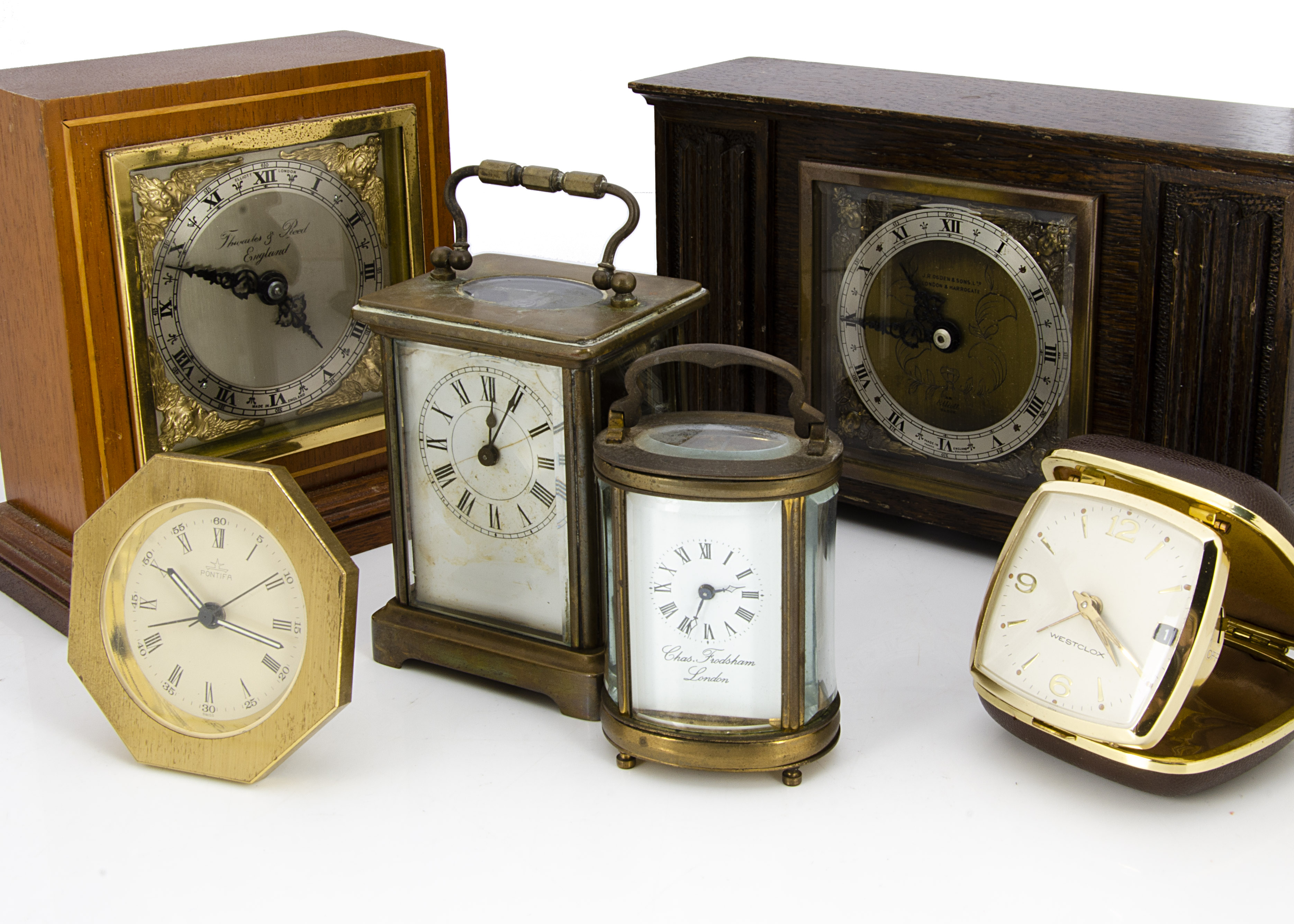 Six vintage and modern timepieces, including a damaged carriage timepiece, a smaller oval carriage