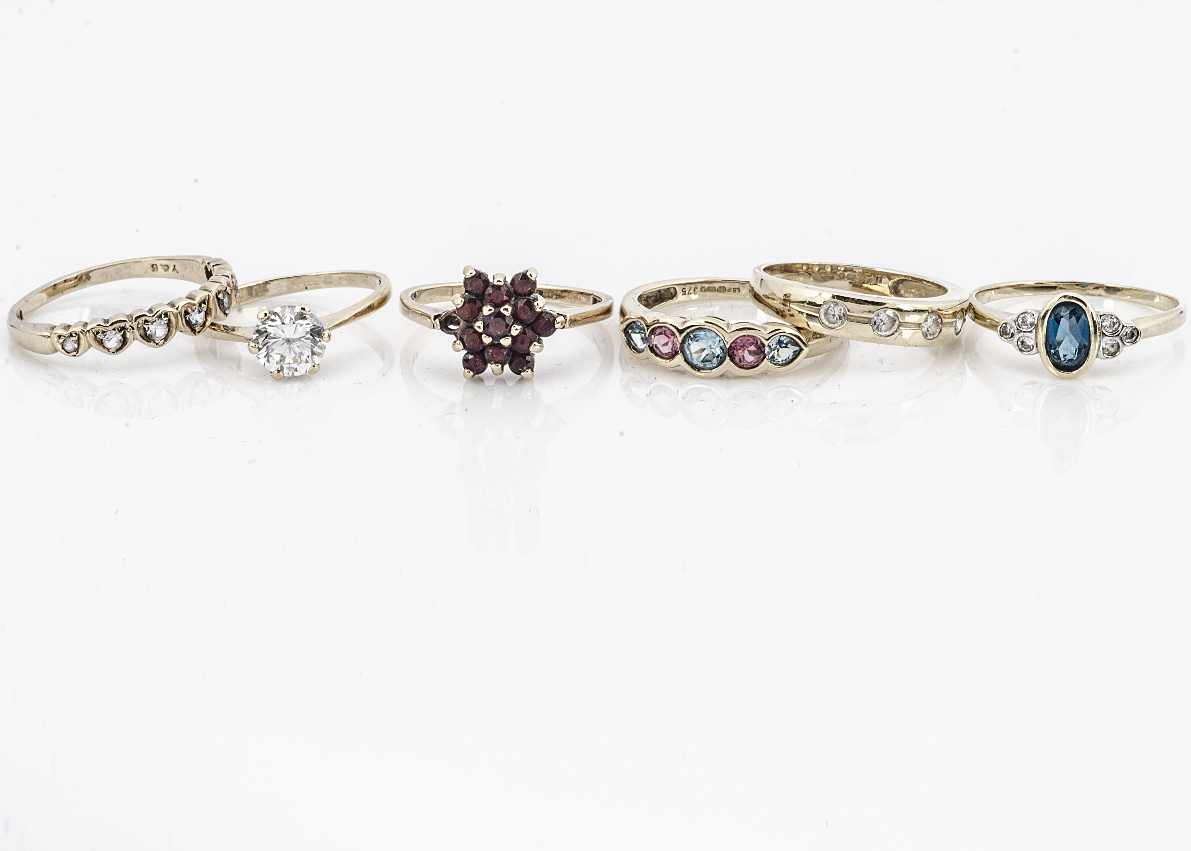 A collection of six 9ct gold gem set dress rings, including a cubic zirconia solitaire, garnet