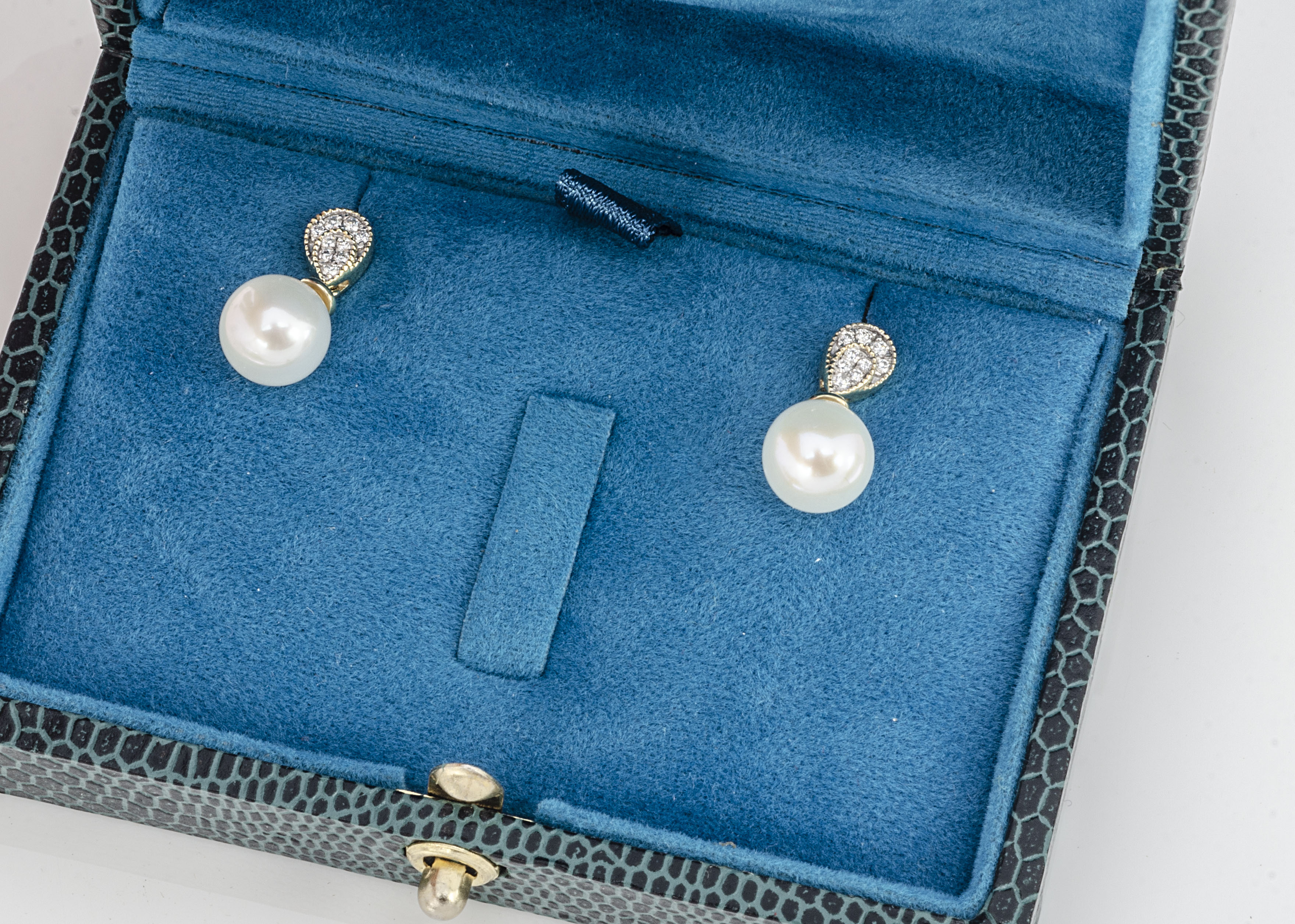 A pair of 9ct white gold diamond and pearl drop studs, the white pearls set in suspended loops on
