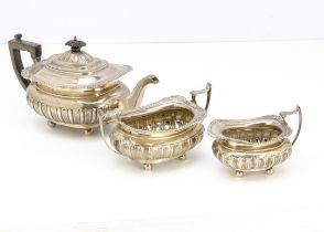 A George V silver three piece tea set by James Deakin & Sons, squat form with feathered and acanthus
