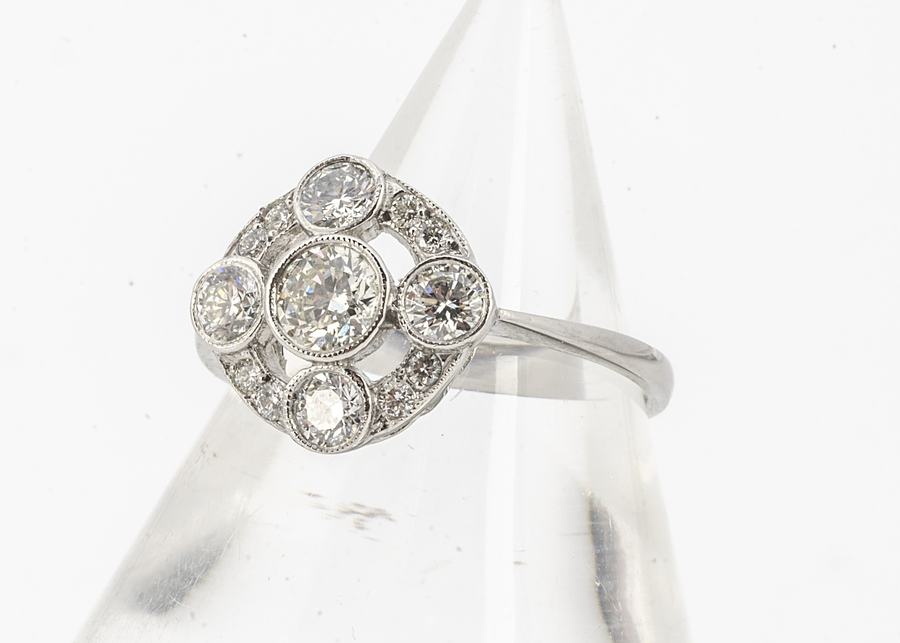 An Edwardian style diamond target ring, all in white metal stamped PLAT, brilliant cuts in colette