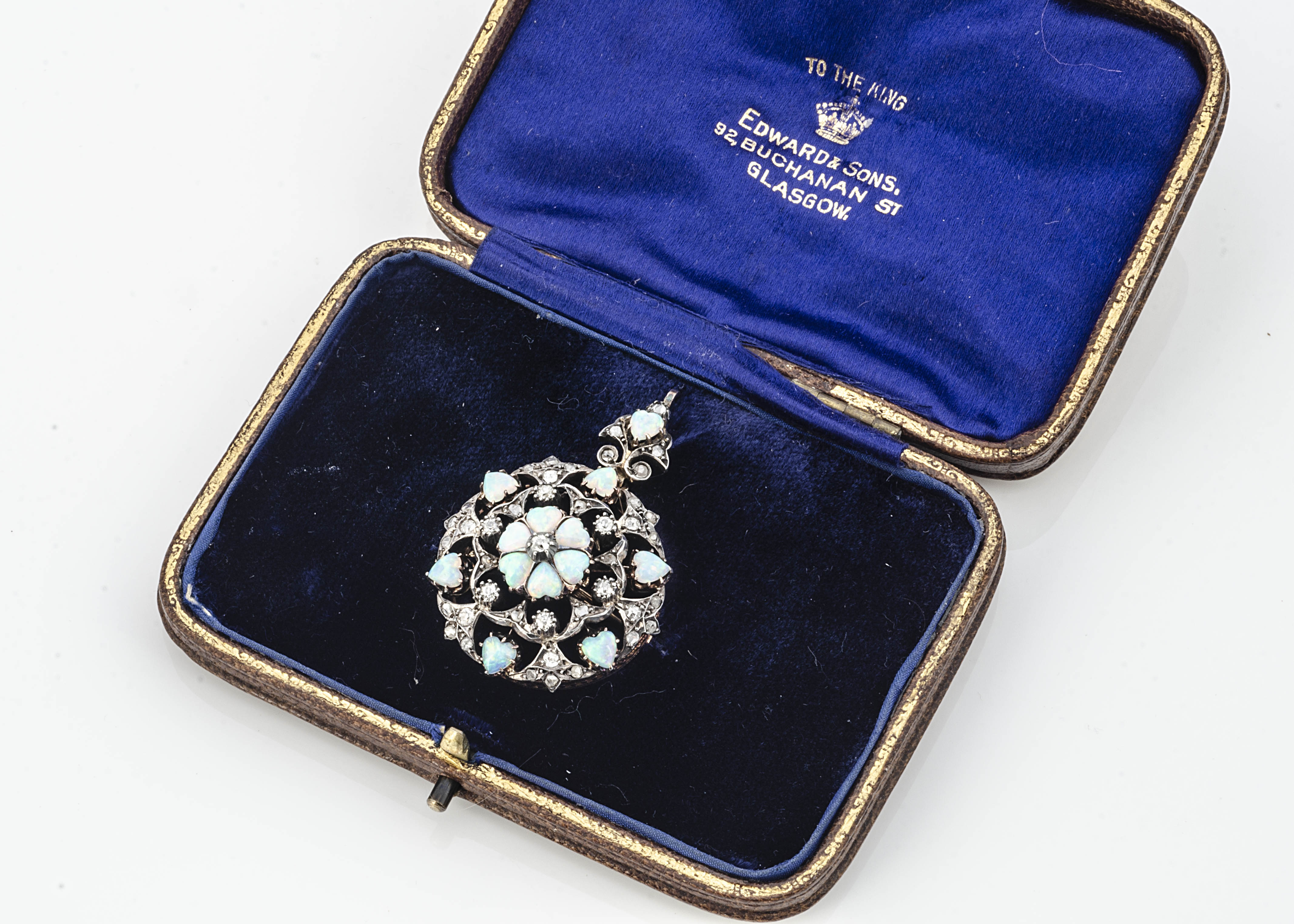 An Edwardian circular opal and diamond brooch or pendant, of target shape with central flower head