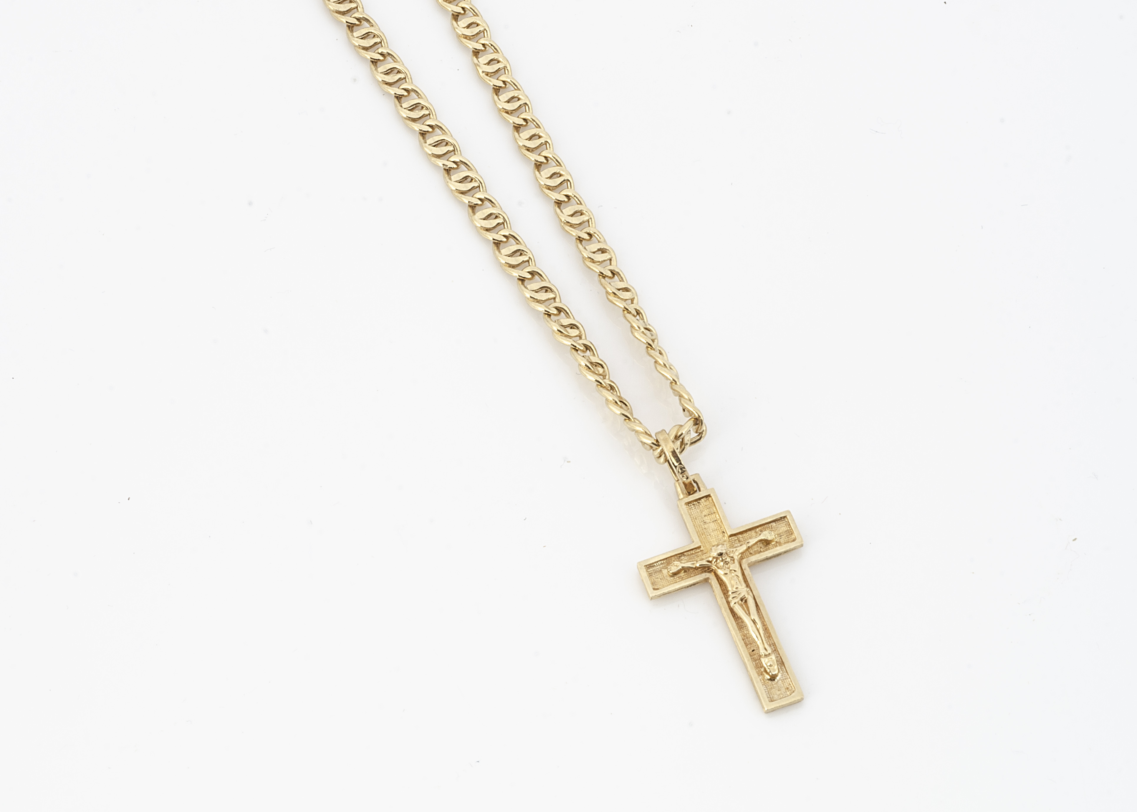A continental yellow metal flattened curb linked chain, with crucifix pendant, all marked 750,