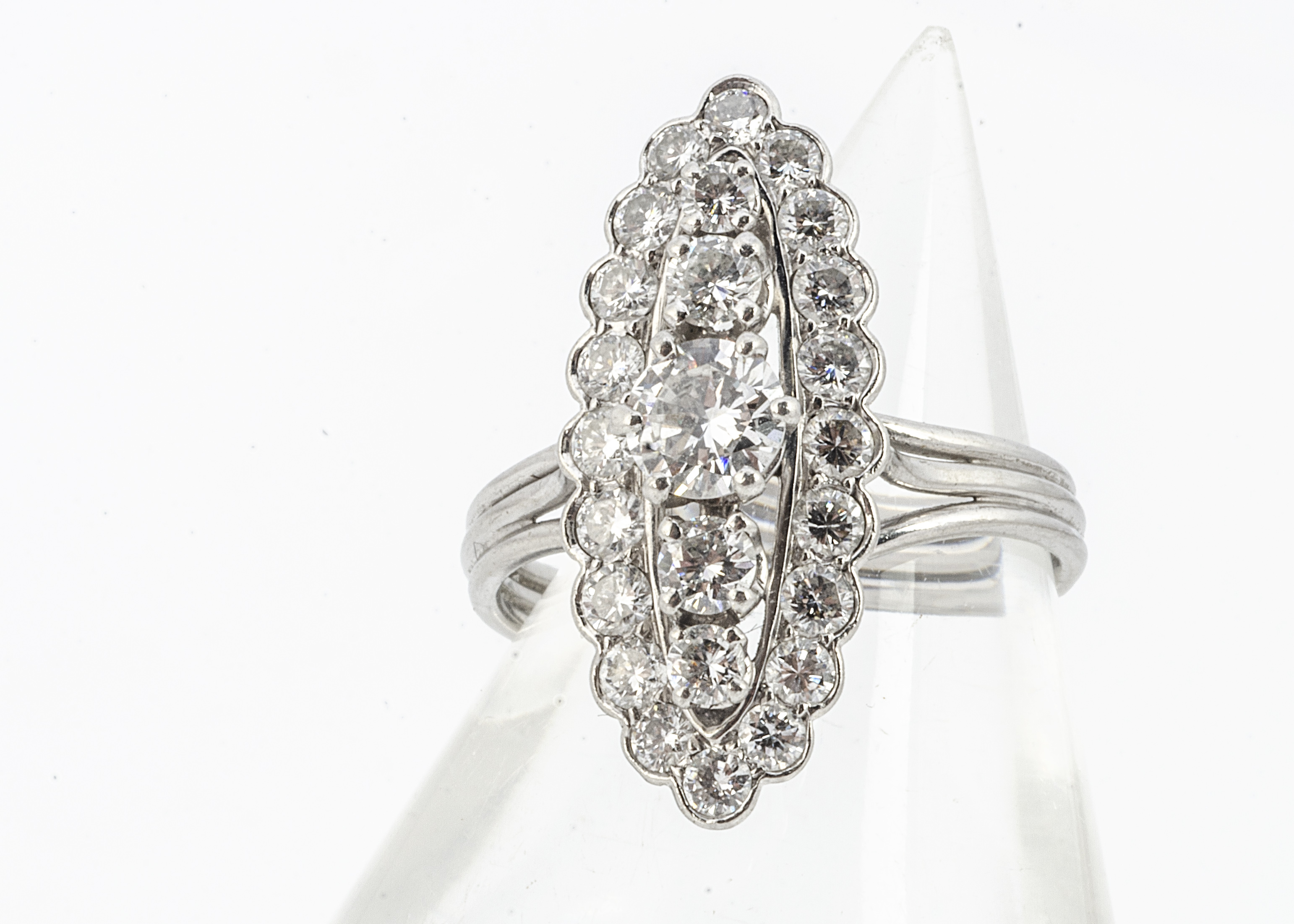 A French diamond set dress ring, of navette shape with a central band of claw set brilliant cut