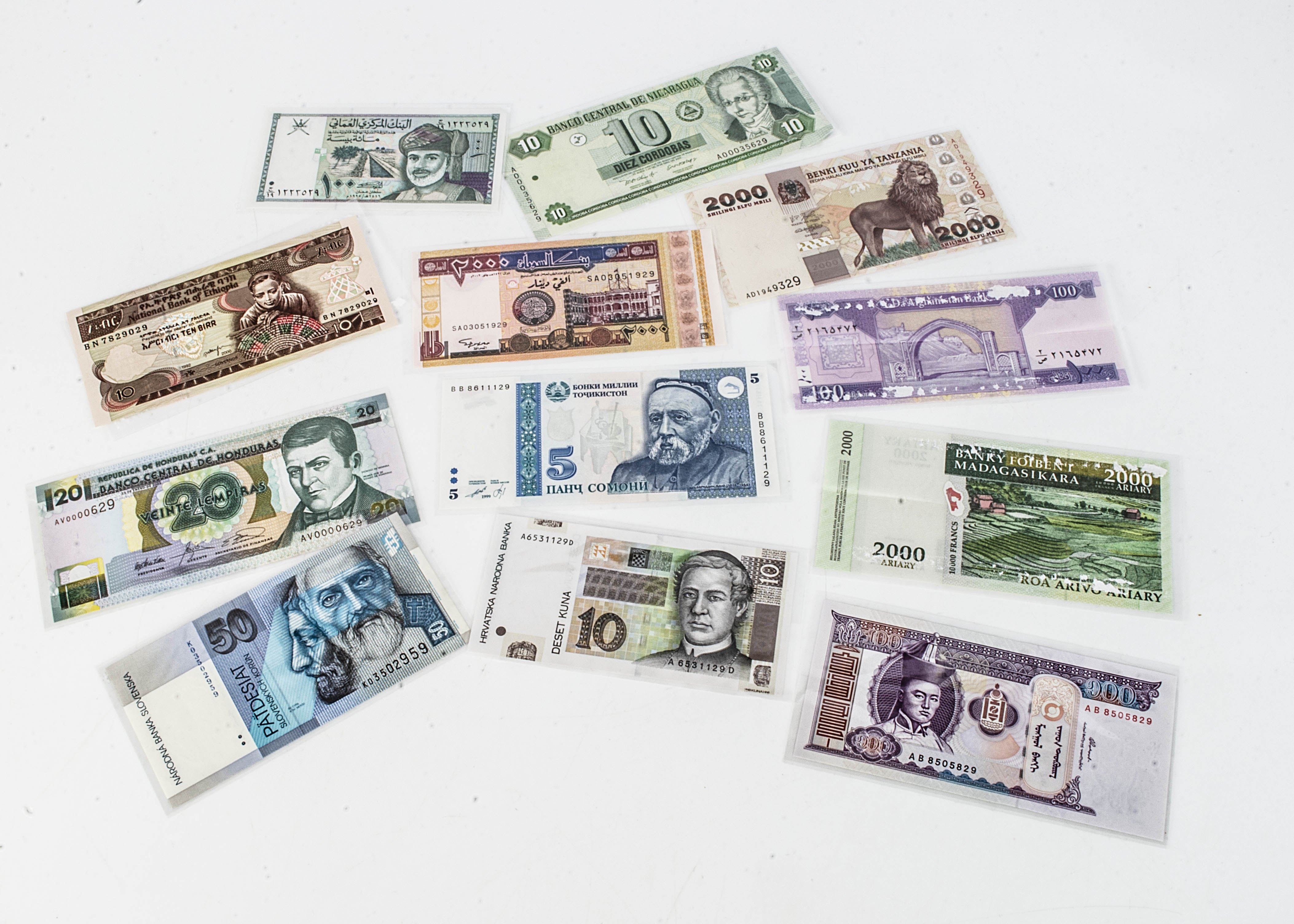 Twelve World bank notes, including 100 from Afghanistan, 2000 shillings from Tanzania, 10 from