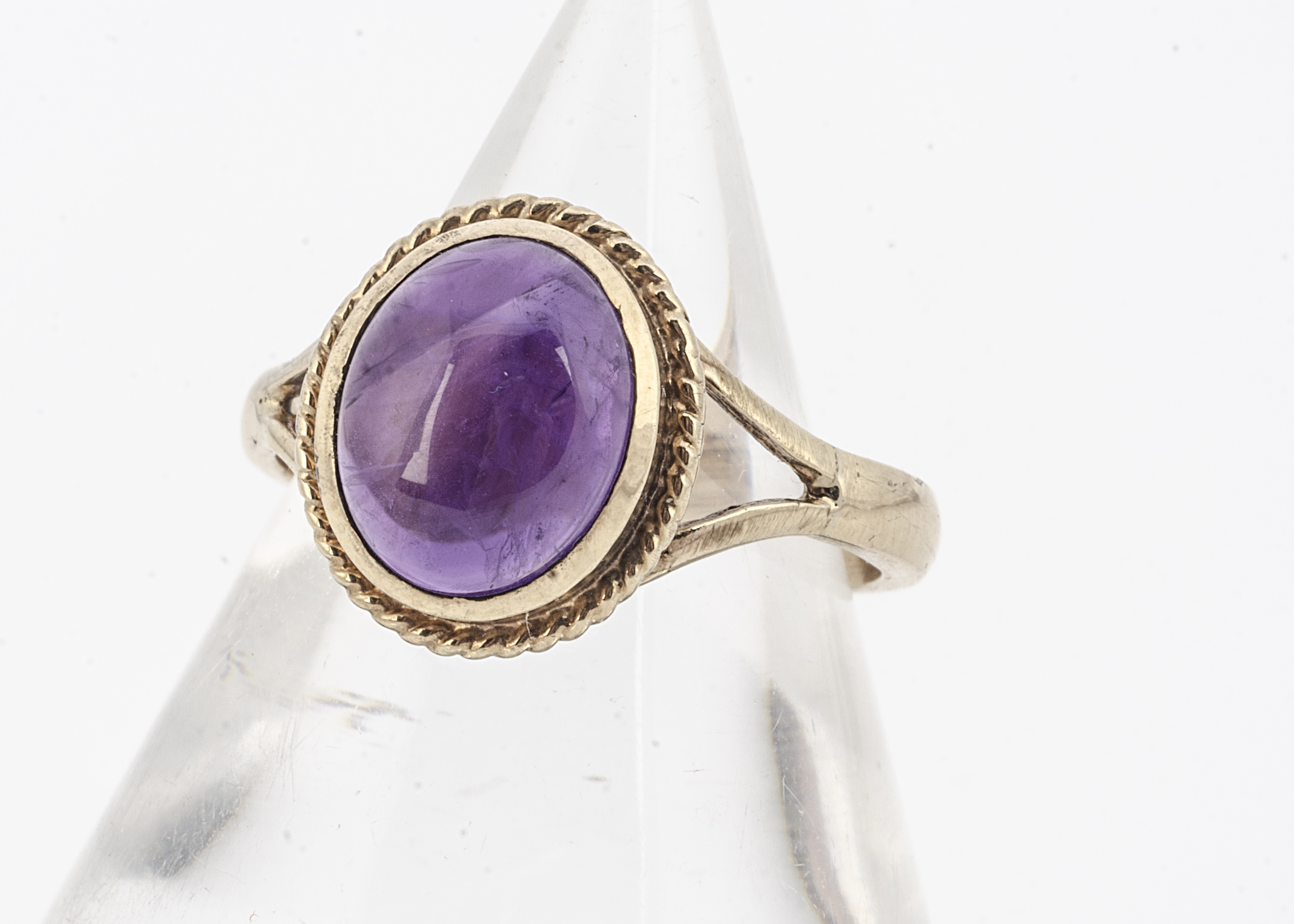 An amethyst cabochon 9ct gold dress ring, the mauve stone with rope twist setting, yellow gold